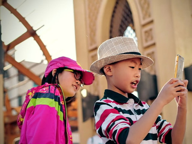 Two children in a city looking at a phone.
