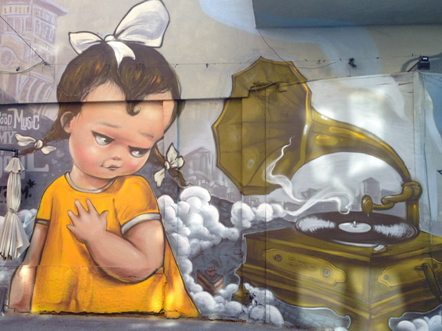 Mural of a young girl with pigtails giving side-eye to a gramophone
