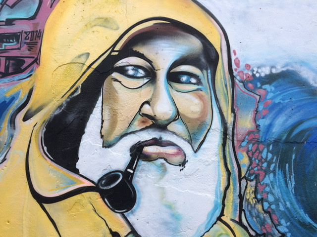 Mural of a fisherman in a yellow rain slicker smoking a pipe