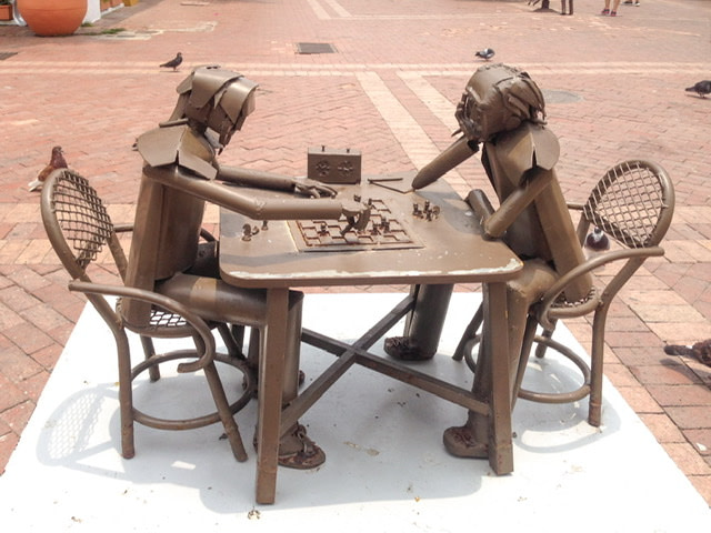 Metal sculpture of two men playing chess