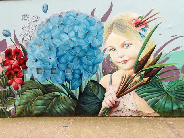 Mural of a girl surrounded by large flowers