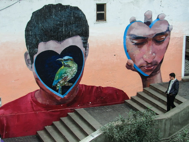 Mural of a boy holding his face next to his head and a bird where his face should be