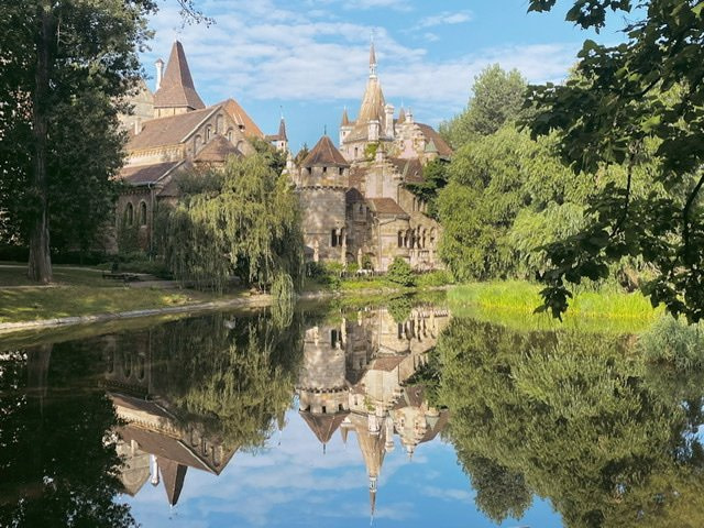 A castle-like building reflected in a pond