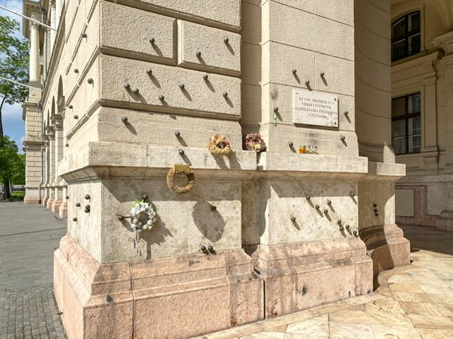A wall with metal balls marking where bullets hit the wall in Budapest