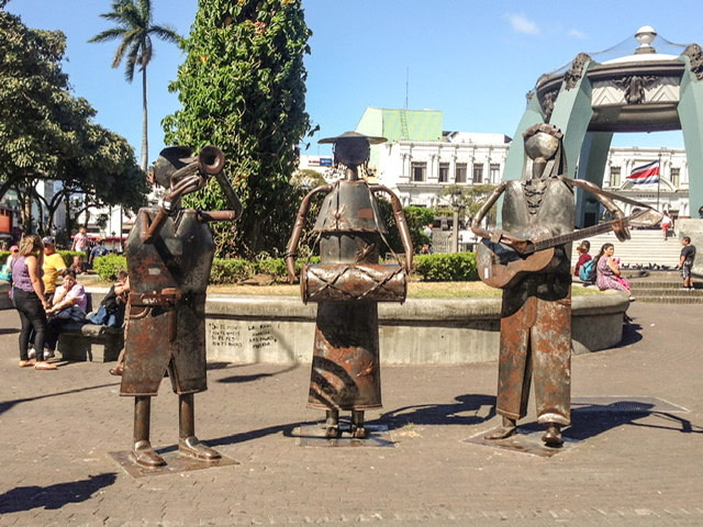 Three life-sized metal sculptures of musicians in a town square