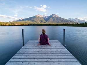 A woman sitting on a dock looking at a lake and mountains