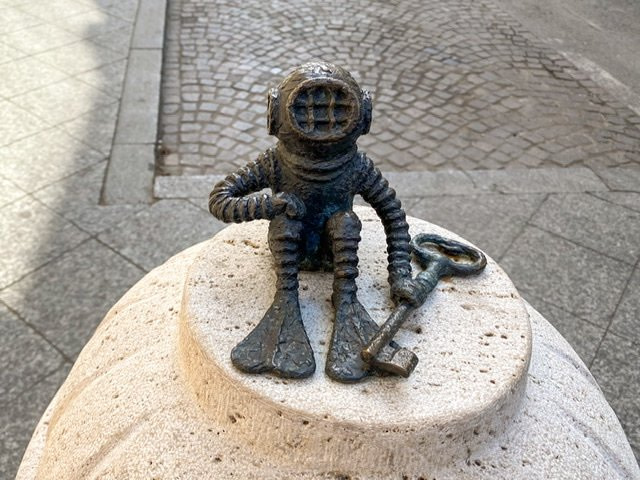 Mini statue of a scuba diver with a key