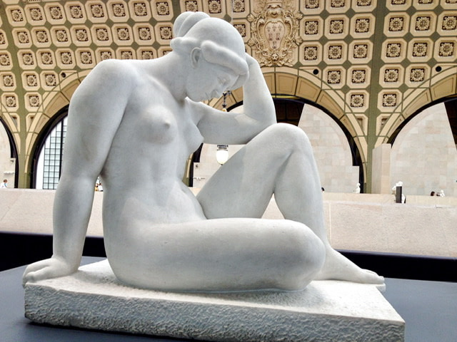 Statue of a nude woman sitting with her head bent forward