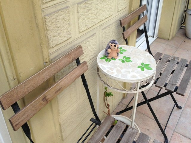 Two chairs and a small table with a stuffed hedgehog on a balcony