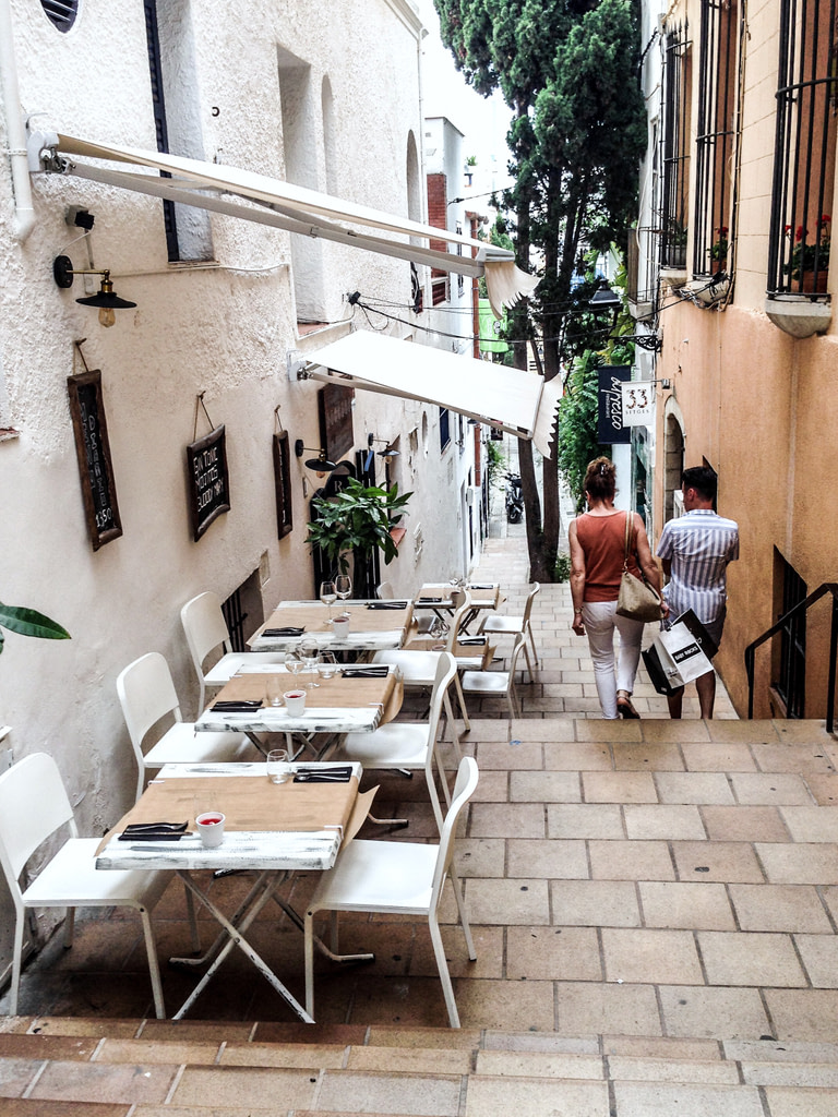 Narrow street with dining tables and chairs in Sitges, Spain