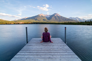 Woman sitting on a dock looking at a lake and mountain