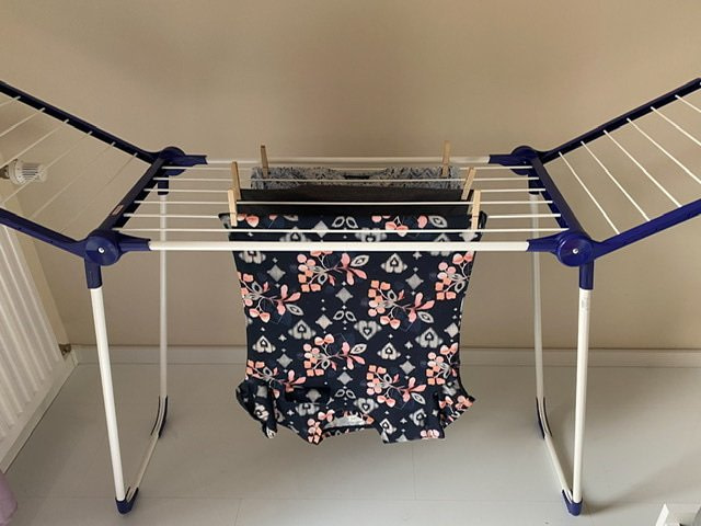 A clothes drying rack with blue shirts