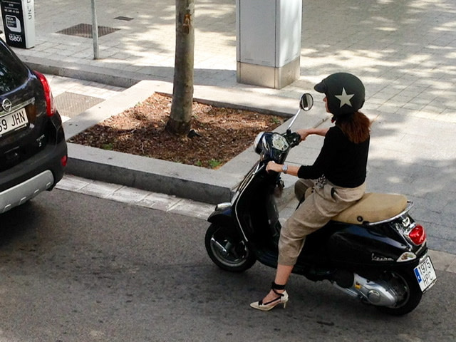 A young woman in high heels riding a scooter