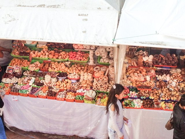 A girl walking by stands of sweets