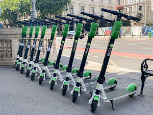 10 electric scooters lined up on a sidewalk