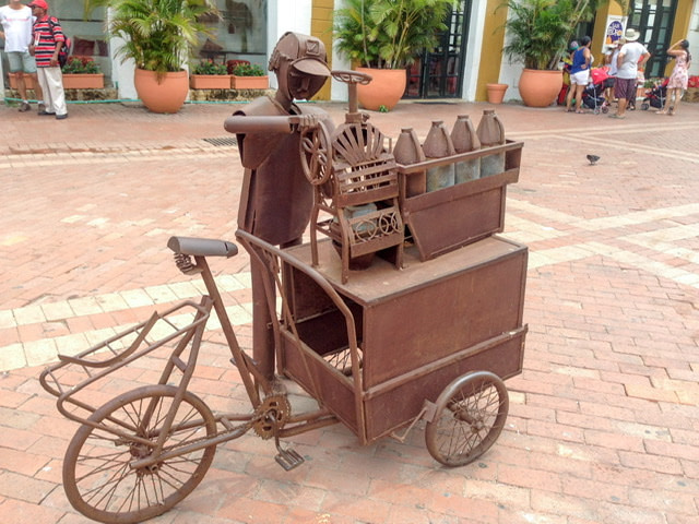 A metal sculpture of a street vendor with his cart
