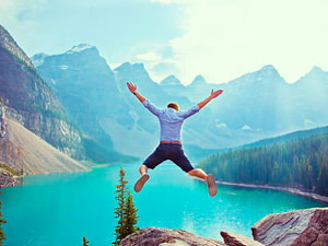 Man jumping into a turquoise lake surrounded by mountains