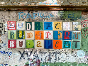 "Colorful tiles spelling out ""Budapest"" three times"