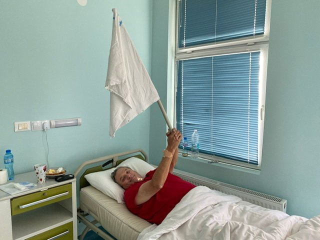 Man lying in a hospital bed waving a white flag
