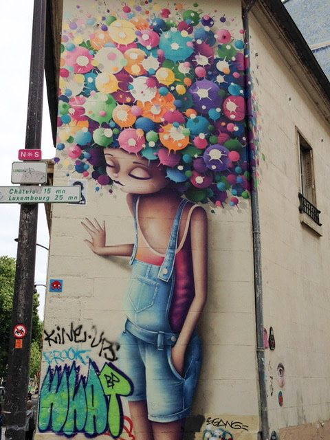 Mural of a girl in overall shorts with colorful balls on her head