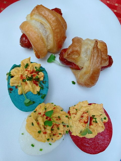 A plate with deviled eggs and pigs in a blanket