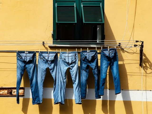 Five pair of jeans hanging on a clothesline