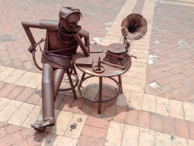 Metal sculpture of a man sitting at a table and listening to a gramophone