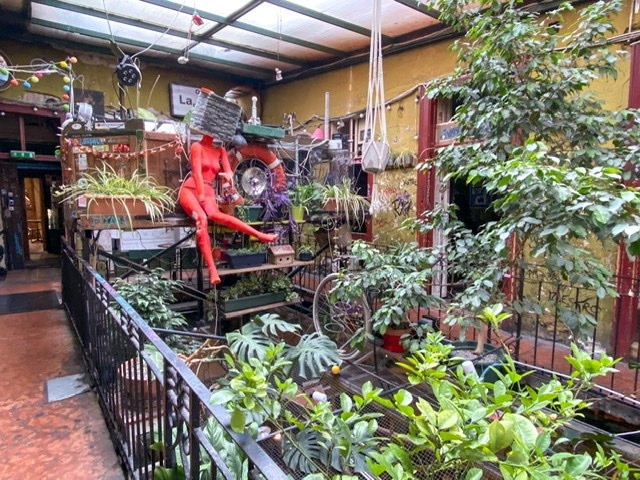 Interior view of Szimpla Kert with plants and mannequin