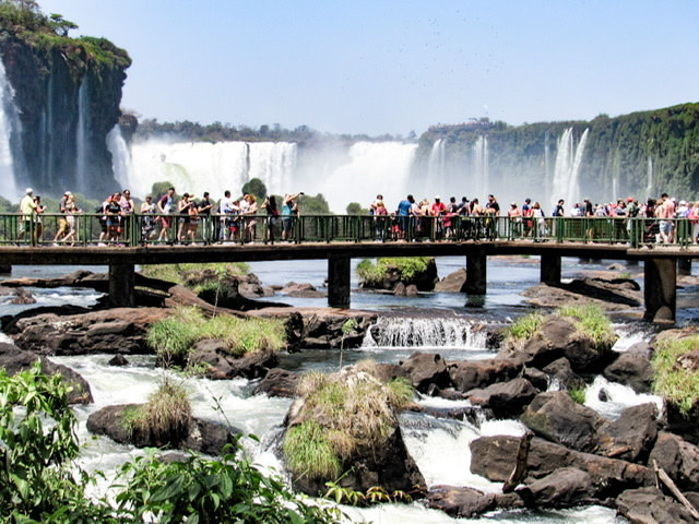 Crowds of people on a boardwalk at Iguazu Falls, Brazil