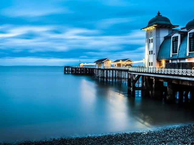 Pier with white buildings and lights at dusk