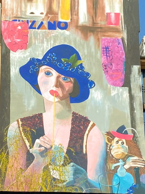 A mural of a woman dring through a straw while sitting next to a monkey
