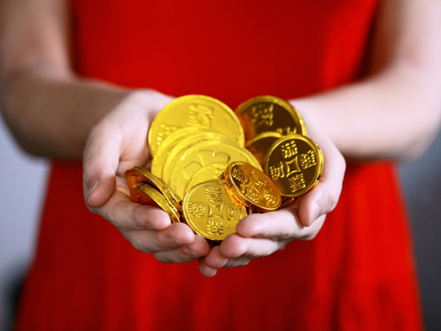 Midsection of a woman in a red dress holding golden coins