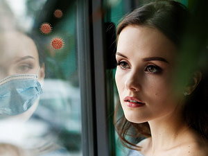 Woman reflected in window with mask and Covid viruses