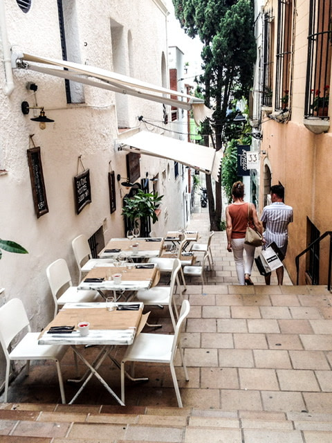 A narrow street with dining tables and chairs in Sitges, Spain