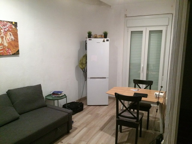 A small living room with a sofa, a table with two chairs, and a refrigerator