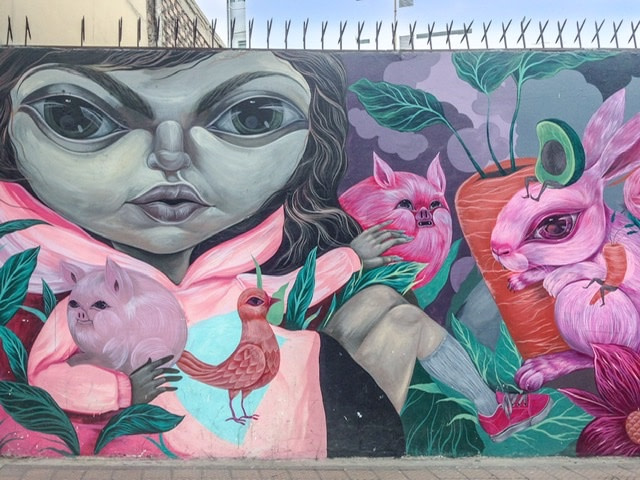 A mural of a girl with two pigs, a bird, and a rabbit