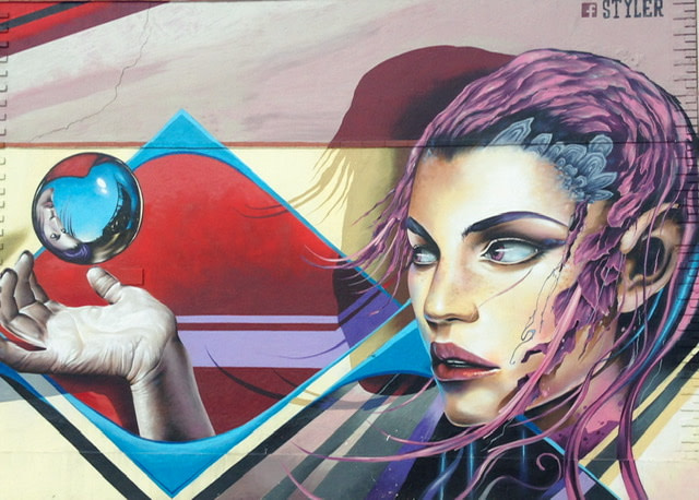 Mural of a woman with purple hair gazing a small crystal ball which is floating above her hand