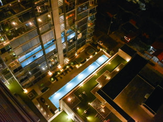 View of a swimming pool reflected in a high-rise building at night