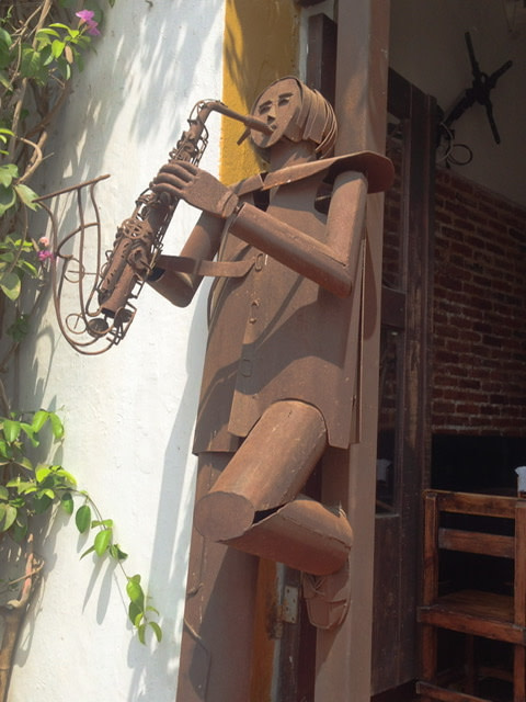 Metal sculpture of a saxophone player leaning against a restaurant door jam