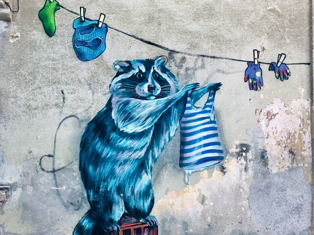 Mural of a blue raccoon hanging up laundry