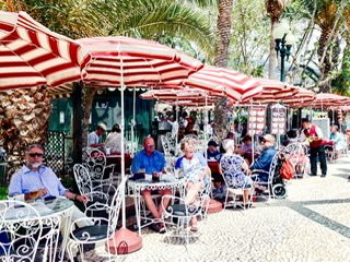 Wrought iron tables with red and white striped umbrellas on a walkway in Funchal, Portugal