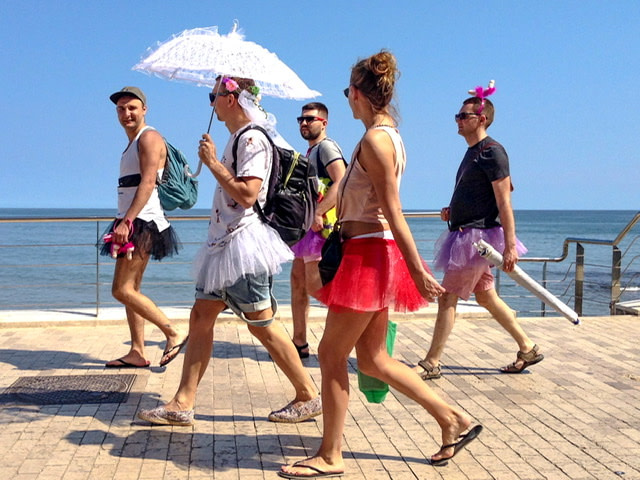 Five people in silly costumes walking on a boardwalk