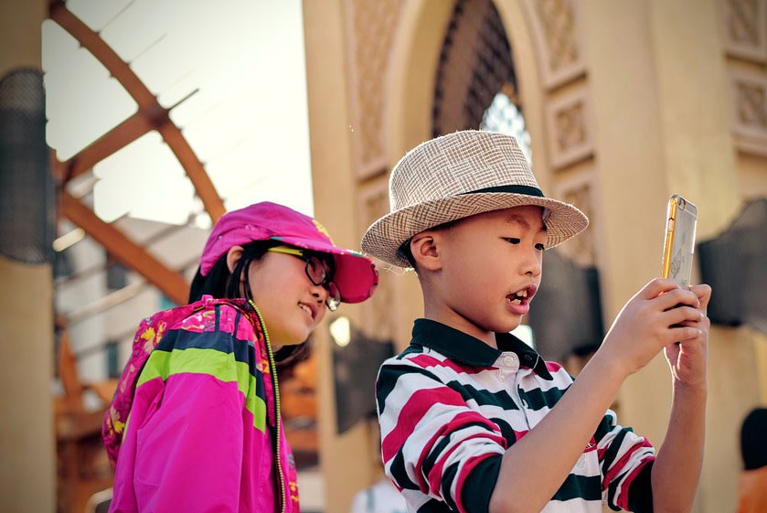 Two children in a city looking at a phone