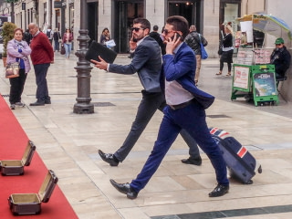 Two men dressed as businessmen performing as human statues