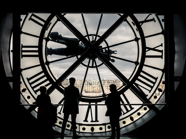 Silhouettes of three people in front of the clock window in the Musee d'Orsay