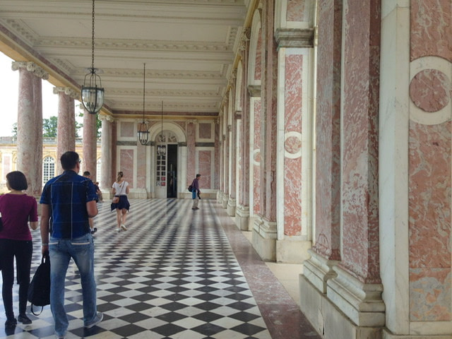 A grand walkway with pink marble columns