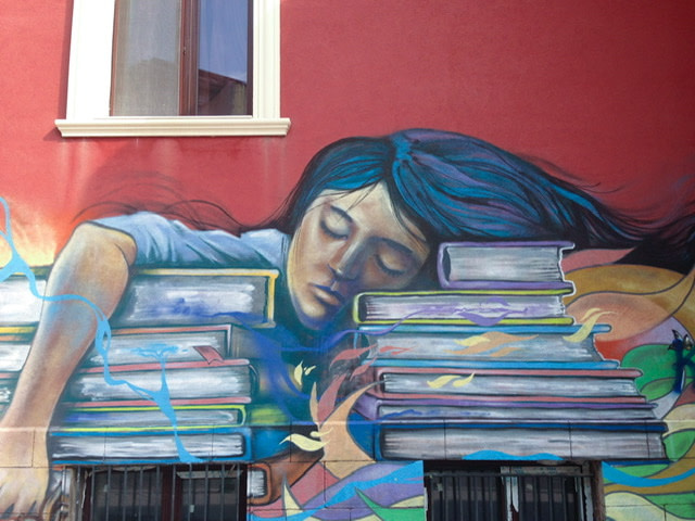 Mural of a girl asleep on a pile of books