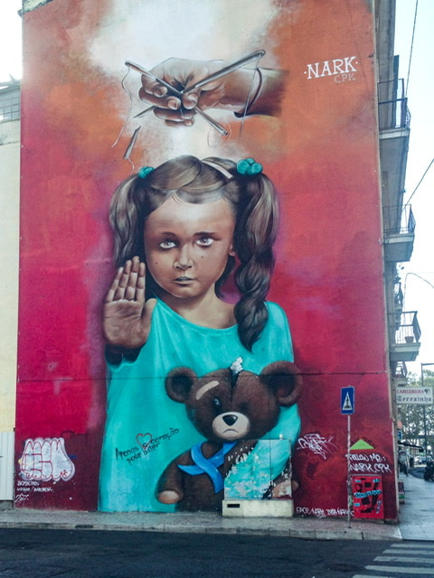 "Mural of a girl holding a teddy bear and putting her hand up in a ""stop"" gesture. A hand is controlling puppet strings attached to her"