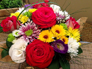 Basket of red, yellow, purple, and white flowers