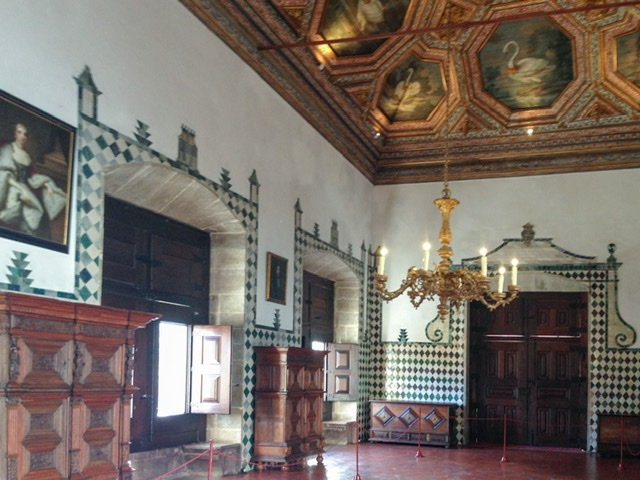 Room with partially tiled walls and swans painted on the ceiling